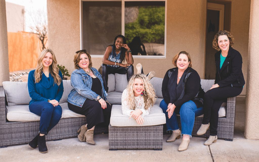 group of women sitting outside on a couch