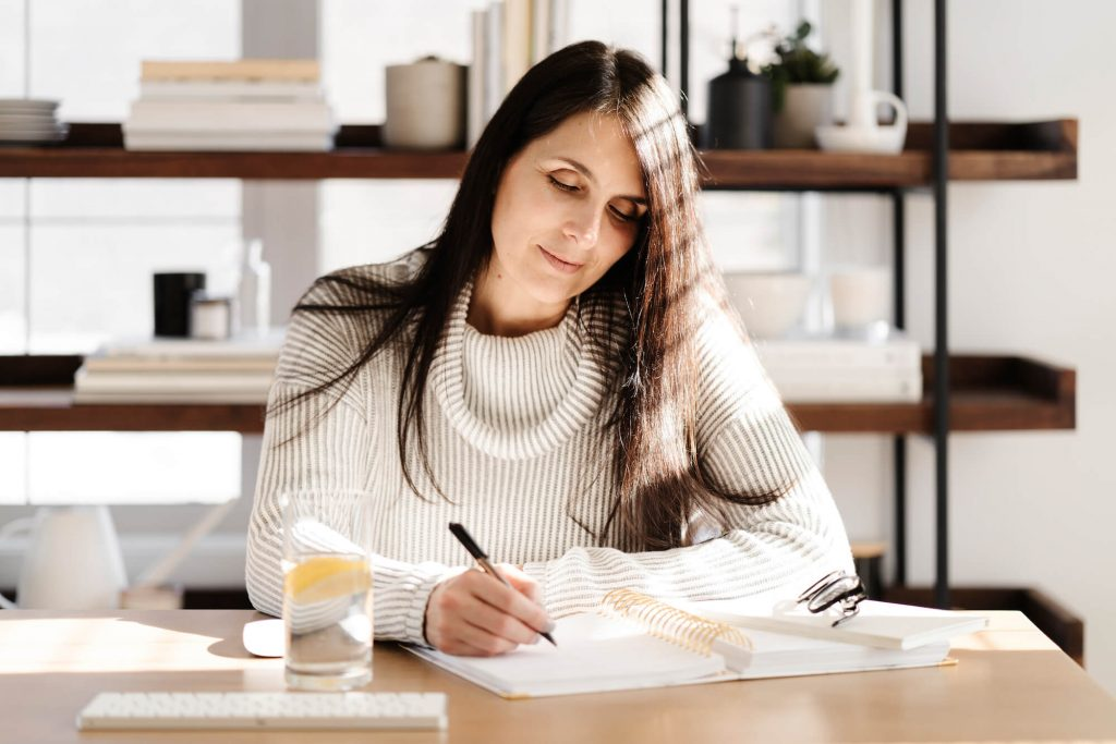 woman sitting at desk writing in notebook