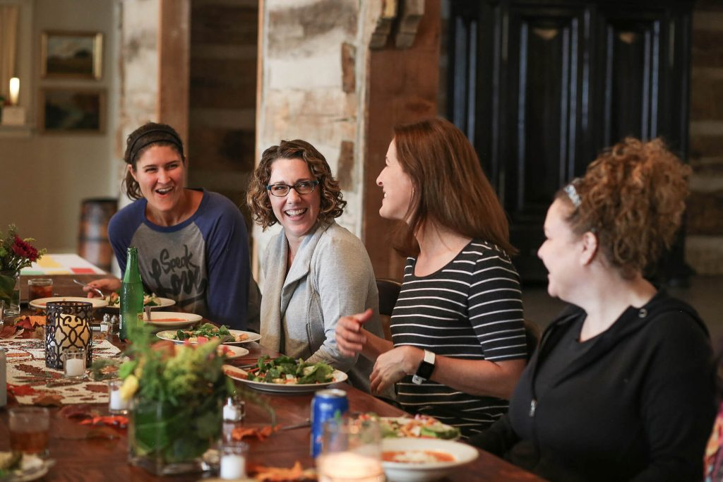 Group of women smiling and laughing at dinner