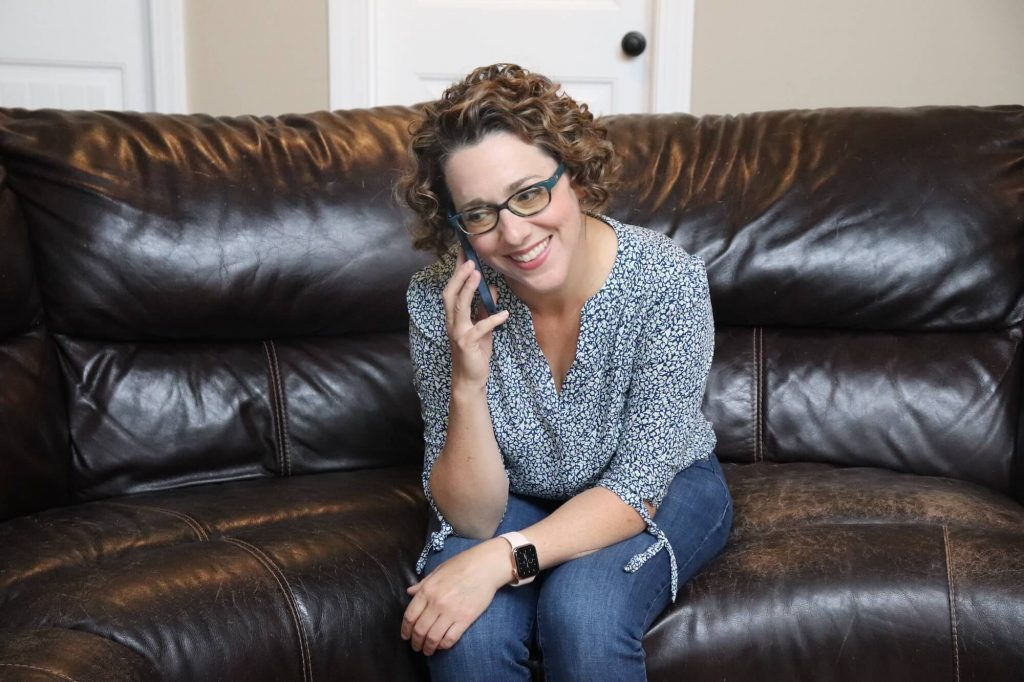 woman sitting on couch talking on phone